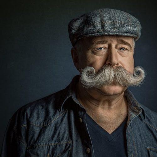Facet z dużymi wąsami w czapeczce
